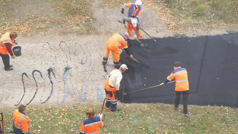 Construction workers during asphalting road. Manual labor in construction Live Action
