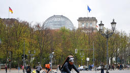 Zoom Out: Cyclists In Front of German Reichstag Building In Berlin, Germany Archivo