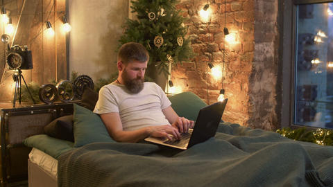 Freelance man lying in bed working with laptop Footage