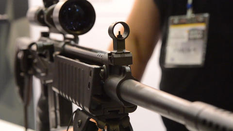 Weapon optics close-up with a man in the back blurred background Footage