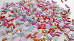 Various Colored Pills Falling Down Onto White Surface With Moving Camera Footage