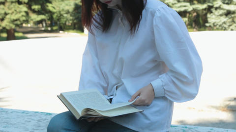 Girl sits and reads a book in the park Footage