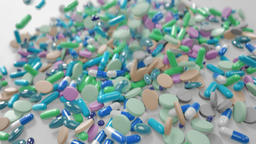 Various Rather Cold Colored Pills Falling Down Onto White Surface Footage