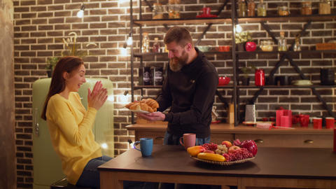 Cheerful man surprising girlfriend with croissants Footage