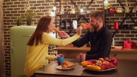 Joyful couple feeding each other with croissants Footage