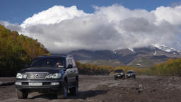Japanese SUV driving on mountain road on dry river in direction of volcano Footage