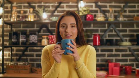 Charming woman enjoying aroma of coffee in kitchen GIF