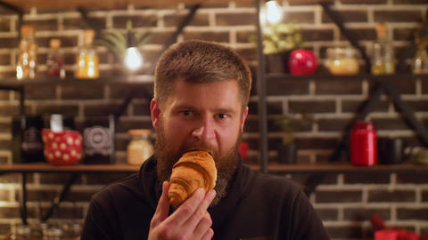 Serious bearded man greedily eating croissant Footage