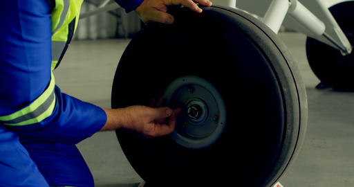 Engineer fixing a wheel of aircraft 4k Live Action