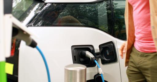 Man charging electric car at charging station 4k Live Action