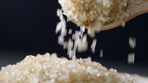 Slow motion closeup shot wooden spoon picking brown sugar in the bowl Live Action