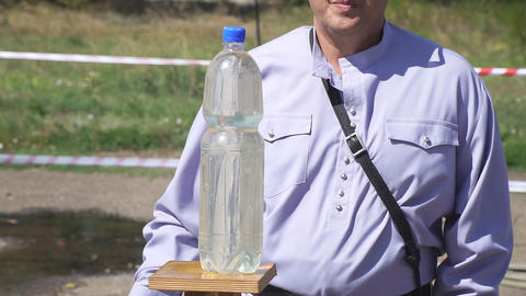 Cossack cuts a plastic bottle with water with a cavalry saber Archivo