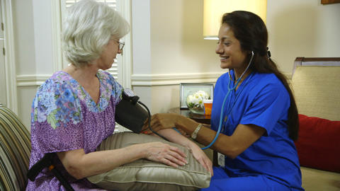 home healthcare nurse starts taking blood pressure of her patient Footage