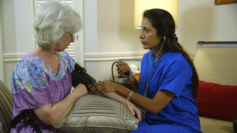 home healthcare nurse taking blood pressure from her patient Footage
