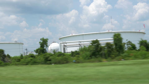 driving view of large petrochemical storage tanks Footage