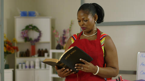 Pan From Flower To Shop Owner Reading Her Bible stock footage