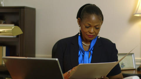 tilt to woman business owner or corporate CEO looking over paperwork file Footage