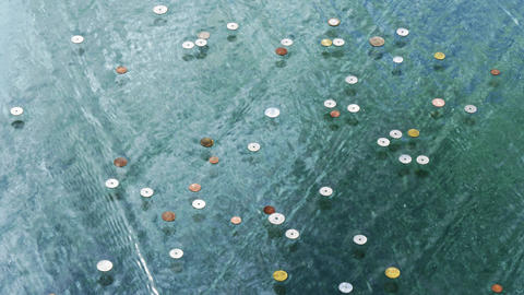 Coins on glass under streaming water Live Action