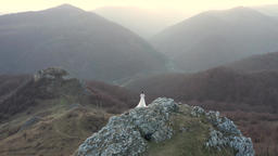 Bride in white wedding dress standing on a cliff. Aerial drone 4k movie GIF