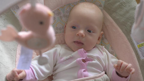 Two months old baby girl under the baby mobile Live Action