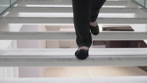 A steadicam shot of female feet going downstairs Live Action