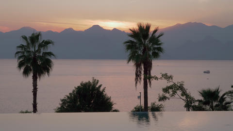 An open swimming pool limit and an evening sea view against the mountains Live Action