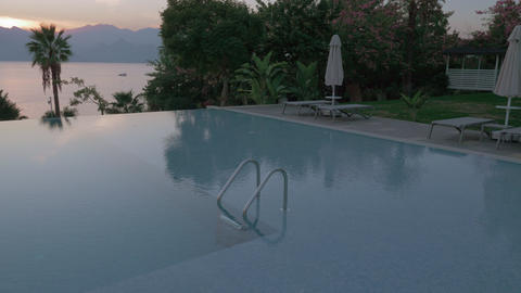 A steadicam shot of an empty open swimming pool with a metal railing Live Action