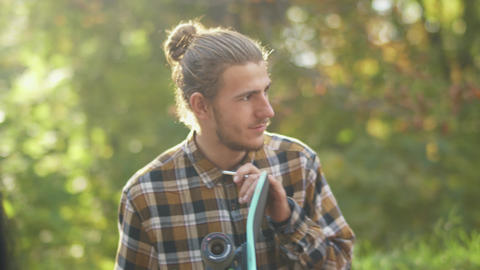 Portrait of a young smiling guy in a plaid shirt customizing a skateboard. Young ライブ動画