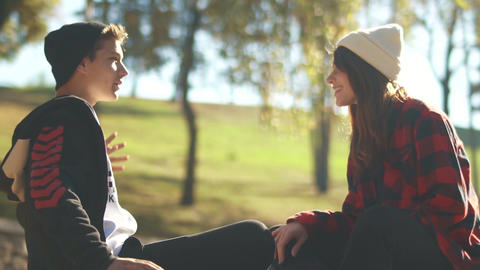 Hipster guy and girl communicate sitting in the sunshine in the park. Teenagers Live Action