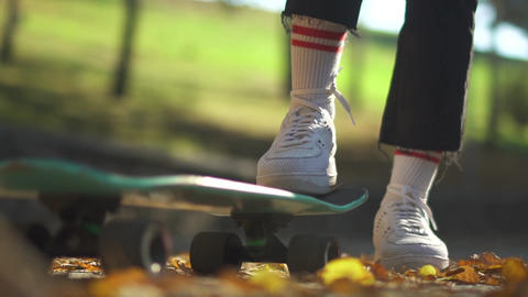 Human foot in white sneakers on a skateboard close-up. Foot in a white sneaker Live Action