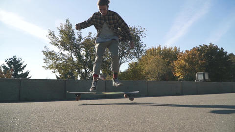 Young hipster guy doing a skateboard trick outdoors. Skateboarder young man in a Live Action