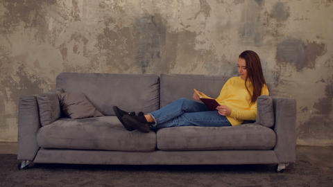 Lovely tired girl with book taking a nap on sofa GIF