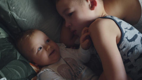 Brother playing with baby sister while in bed Footage