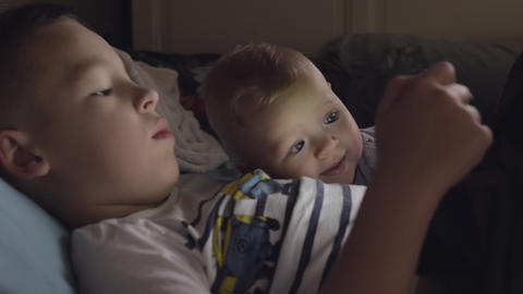 Brother on a tablet with younger baby sister Live Action
