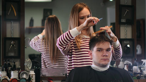 Close-up hairdresser with scissors and comb. Blurred background Footage