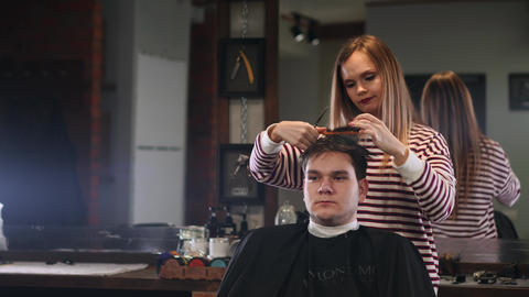 Female hairdresser cutting hair of smiling man client at beauty parlour Live Action