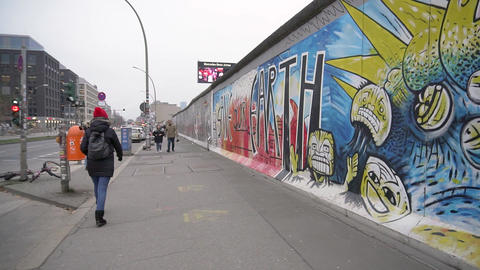 BERLIN, GERMANY - NOV 22, 2018: Trendy tourist walks near Berlin Wall. Slow Live Action