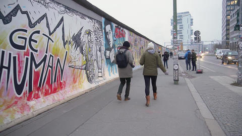 BERLIN, GERMANY - NOV 22, 2018: Young couple walks near Berlin Wall. Slow motion Live Action