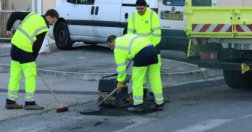 Three Workmen Repairing A Road Surface Live Action
