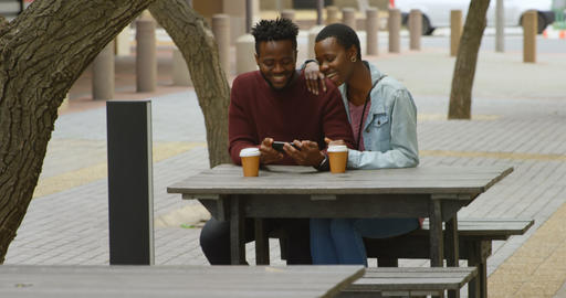 Couple using mobile phone in outdoor cafe 4k Live Action
