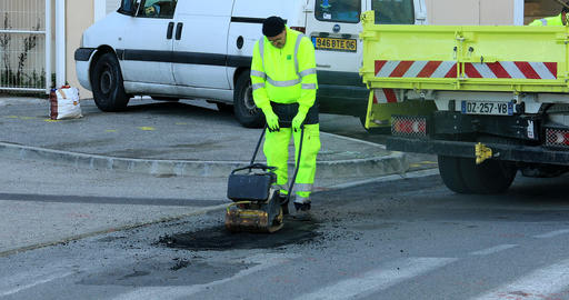 Road Repair Vibrating Machine Pushed By A Worker Live Action