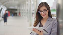 Business woman using tablet computer, looking to camera GIF