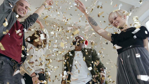 Happy young people are dancing throwing gold confetti at celebration party Footage