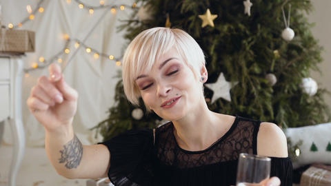 Young smiling woman with short hair is celebrating New Year with sparkling wine Footage