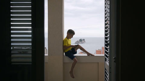 A young boy use his tablet for playing game while sits down on balcony at home Footage
