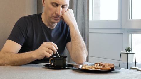 Adult man in the morning in the kitchen, thinking about their problems. He is GIF