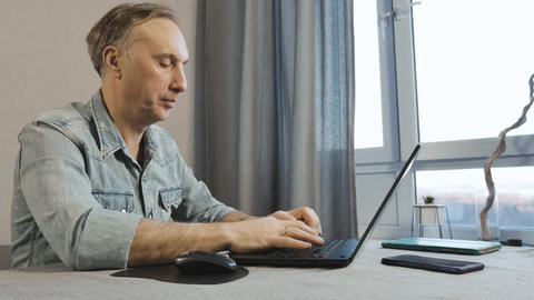 A middle aged man working on a laptop. Freelancer works at home Footage