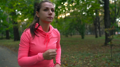 Close up of woman tying shoe laces and running through an autumn park at sunset Footage