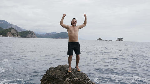 A person rejoices in life by raising his hands up standing on a rock by the sea Footage