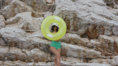 Slim beautiful brunette in a green swimsuit and a big hat smiles at the camera Footage